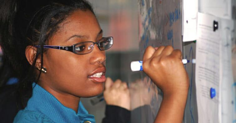 Black, female Amistad High School student writing on whiteboard