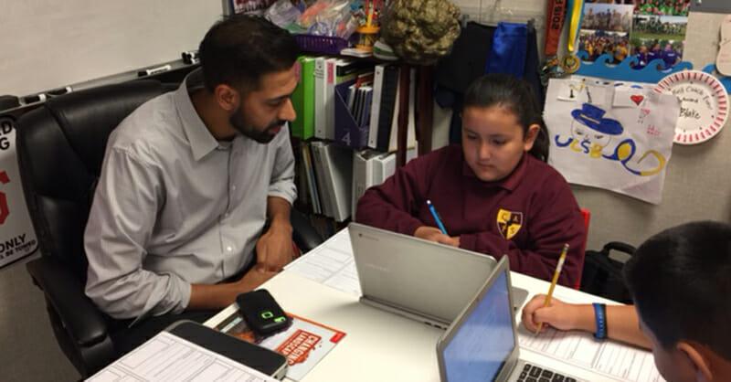 Cornerstone Academy teacher helping Latina student